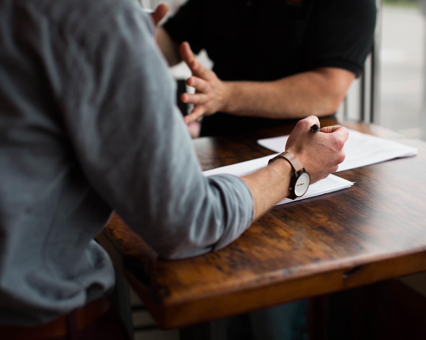 Dos personas hablando en una reunión tomando notas